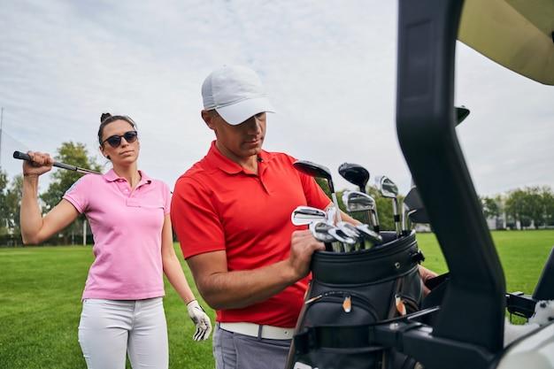 Slim dark-haired caucasian female golfer in sunglasses standing behind her personal trainer in a cap