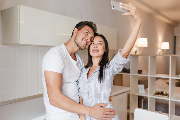 Slim dark-haired woman making selfie with husband before breakfast