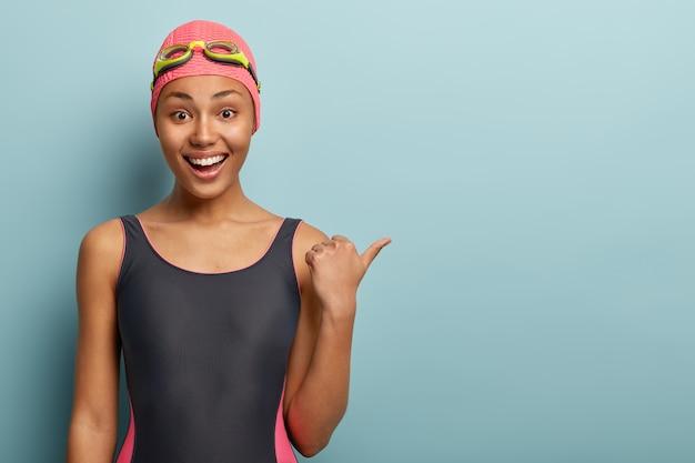 Slim dark skinned female swimmer in black bathingsuit, points thumb on free space