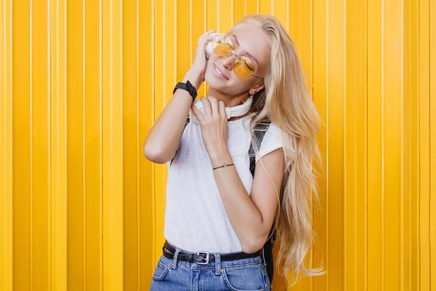좋은 하루를 즐기고 긴 빛나는 머리를 가진 슬림 꿈꾸는 여자. 노란색 배경에 포즈 흰색 t- 셔츠에 사랑스러운 무두 질된 여자의 초상화.