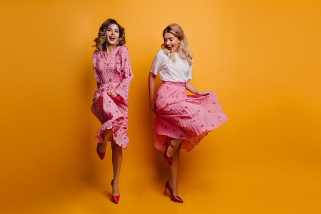 Slim ragazza eccitata che balla con l'amica debonair signore indossa abiti rosa che si rilassano insieme sul muro giallo.