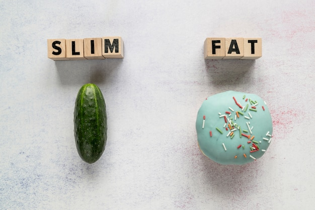 Slim; fat text on wooden blocks with cucumber and glazed donut over rough backdrop