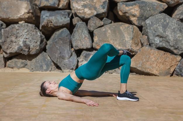 石垣の近くで運動するスリムな女性アスリート