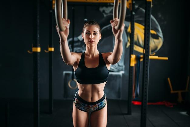体操リングのスリムな女性アスリートトレーニング。フィットネスクラブでの女性体操