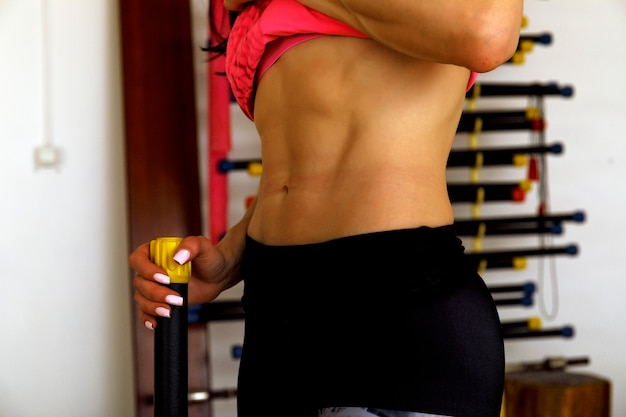 Slim female athlete trains press in sport gym. sporty girl showing her well trained body