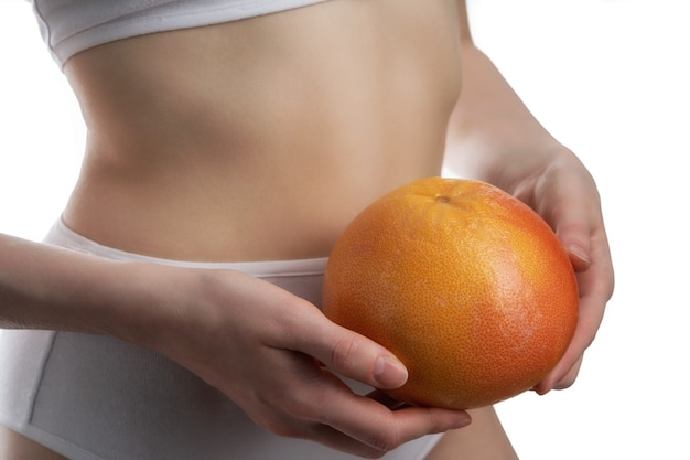 Slim female belly and grapefruit isolated on white surface