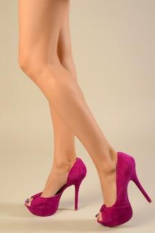 Slim female feet in pink suede high-heeled shoes