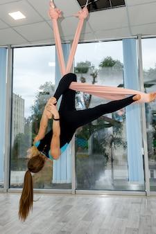 Стройный женский инструктор показывает практику йоги на гамаках в фитнес-студии. упражнения йоги для здорового образа жизни