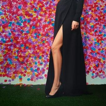 Slim female legs in long dress with deep cut