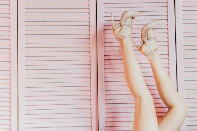 Slim female legs in nude colour shoes on pink. fashion art photo. fashion shoes