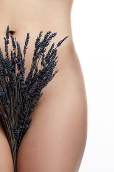 그녀의 다리 사이에 라벤더 꽃다발과 함께 슬림 여성 알몸. 몸과 건강을 돌봅니다. 흰색 배경. 수직의.