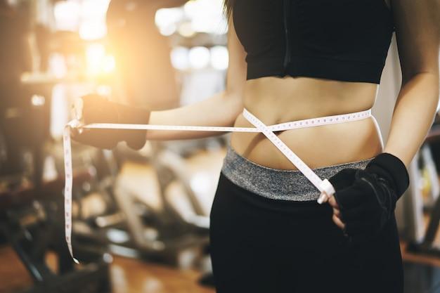 ジムで腰に巻き付ける測定テープを使用してスリムな女性。スポーツ、フィットネス、ダイエット結果、アクティブなライフスタイル。