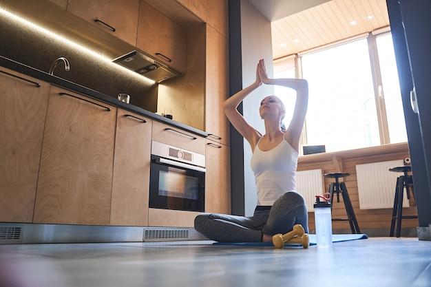 Slim female yogi in a tank top and leggings sitting crossed-legged on the kitchen floor
