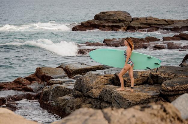 대서양 해변에서 바위에 서핑 보드와 함께 서있는 멀티 컬러 수영복에 슬림 그림 소녀