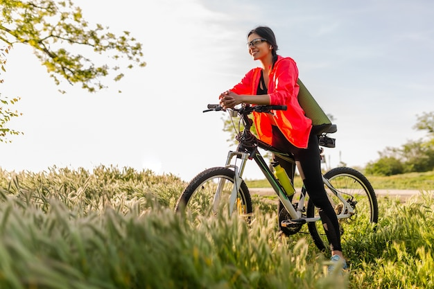 Стройная красивая женщина занимается спортом утром в парке, катается на велосипеде с ковриком для йоги в красочной фитнес-экипировке, исследует природу, улыбается, счастливый здоровый образ жизни