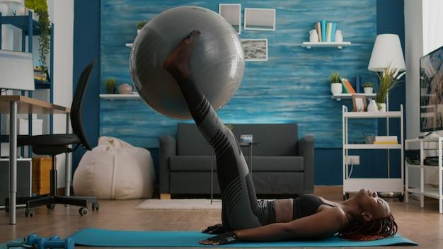 슬림 맞는 흑인 여성은 바닥에 누워 복부 근육 프레스를 펌프