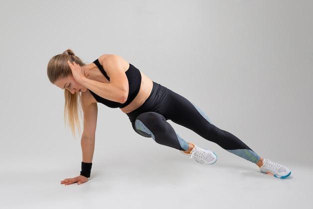 Стройная блондинка в униформе занимается фитнесом на сером фоне