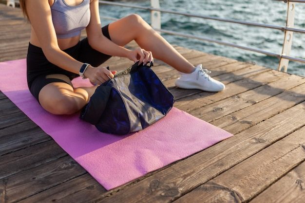 ビーチで朝のトレーニングの準備をしているスリムフィットの女性は彼女のトレーニングバッグを解凍します
