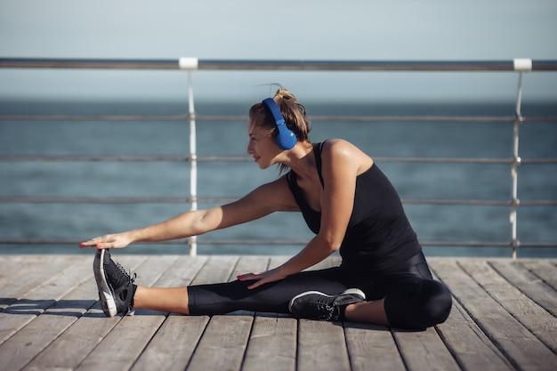 운동복에 슬림 맞는 여자 다리 스트레칭을하고 헤드폰으로 음악을 듣고
