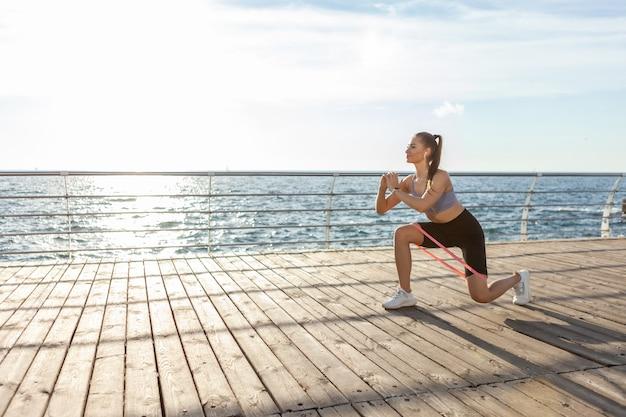 일출 때 해변에서 피트니스 고무 밴드와 함께 운동복 운동을 하는 날씬한 여성