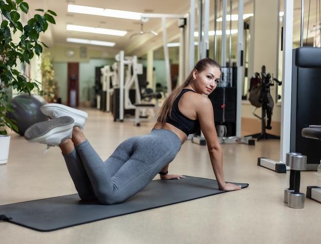 Slim fit женщина в спортивной одежде готовится делать отжимания от пола в тренажерном зале. концепция здорового образа жизни
