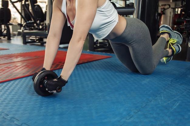 ジムでabホイールを使って運動を練習しているスポーツウェアのスリムフィットの女性