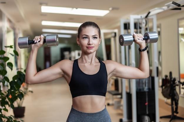 운동복에 슬림 맞는 여자 체육관 방에 손에 아령와 보도. 건강한 라이프 스타일 컨셉