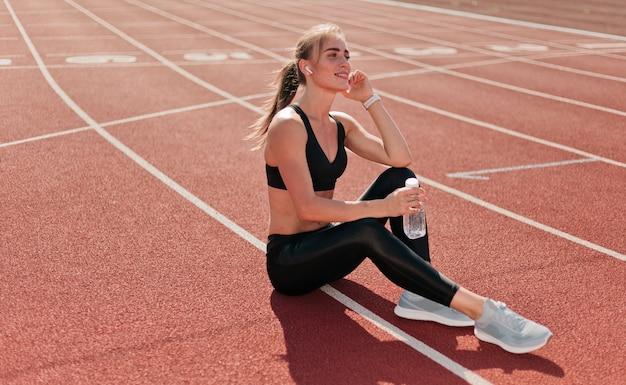 야외에서 빨간 코팅 경기장 트랙에 앉아있는 동안 이어폰으로 음악을 듣고 sportwear에 슬림 맞는 여자. 달리는,