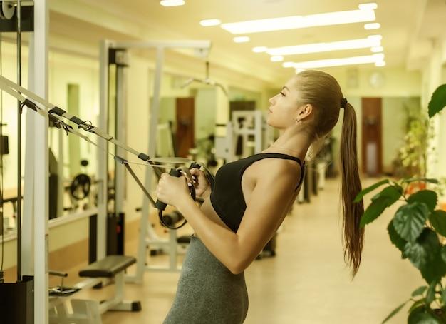 날씬한 여성이 체육관에서 피트니스 스트랩으로 훈련하고 있습니다. 건강한 라이프 스타일 개념입니다. 기능 훈련