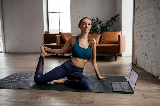 온라인 수업 또는 가상 튜토리얼을 위해 노트북을 사용하여 집에서 요가를 연습하고 몸을 스트레칭하는 슬림 한 여성. 고품질 사진