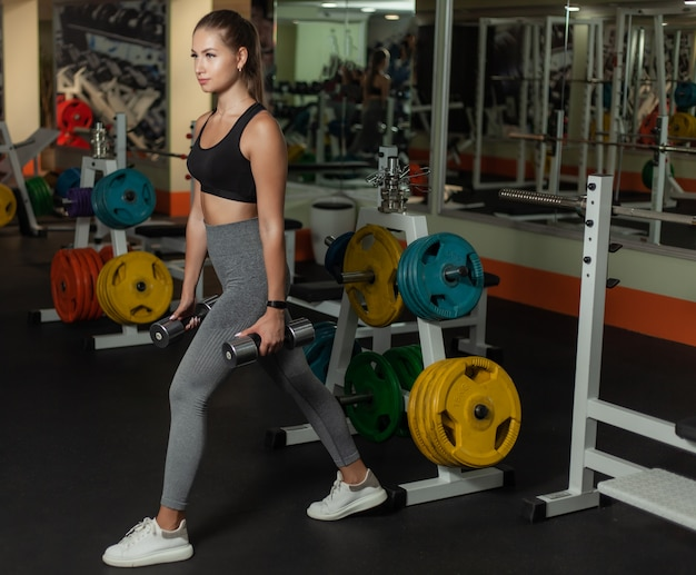 Slim fit woman in sportswear lunges with legs with dumbbells in her hands in the gym. healthy lifestyle concept
