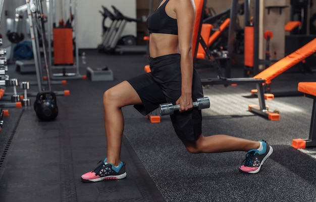 Slim fit woman in sportswear practicing lunges with dumbbells in her hands in the gym. training concept with free weights. functional training