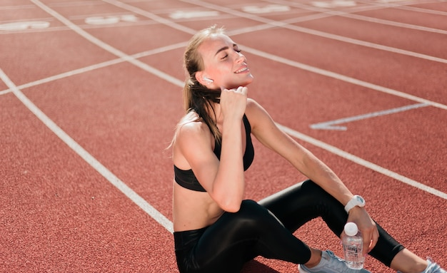 Slim fit woman in sportwear listening to music with earphones while sitting on a stadium track with a red coating in the open air. running,
