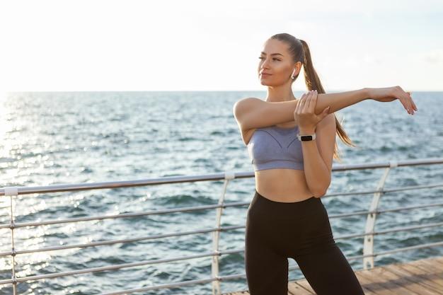 完璧なボディのスリムフィットの女性は、日の出のビーチでトレーニングする前に手のストレッチを練習しています