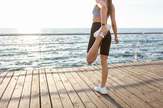 完璧なボディのスリムフィットの女性は、日の出のビーチでトレーニングする前に脚のストレッチを練習しています