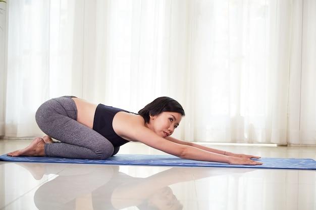 Стройная молодая азиатская женщина делает упражнения на растяжку на коврике для йоги дома