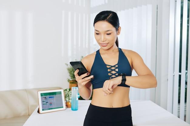 自宅でのエクササイズを終えた後、スマートウォッチ、スマートフォン、タブレットコンピューターでアプリケーションを同期するスリムフィットの若いアジア人女性