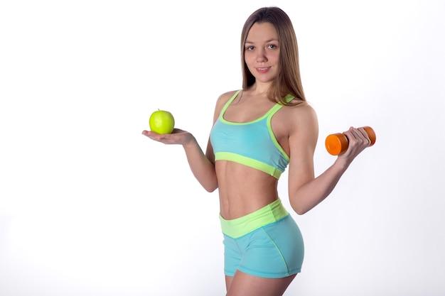 Стройная женщина фитнеса позирует с яблоком и гантелями