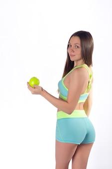 スリムなフィットネスの女性がリンゴ、背面図でポーズ
