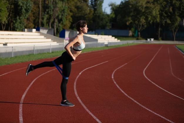 スリムなフィットネスの女性がスタジアムの屋外で輪ゴムでウォームアップします。空きスペース