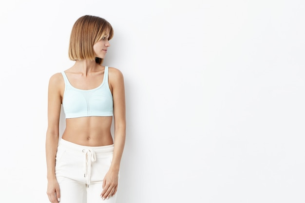 흰색 위에 바지를 입고 슬림 피트니스 젊은 여성, 절연, 스포츠 훈련을하기 위해 체육관에가는, 경쟁을 준비, 사려 깊은 표정으로 옆으로 찾고