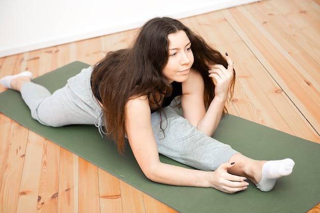 Стройная молодая девушка фитнеса практикует упражнения йоги релаксации в помещении дома. спорт, здоровый образ жизни.