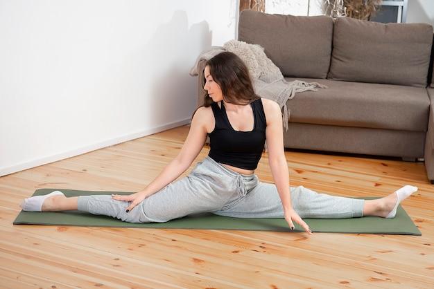 Стройная молодая девушка фитнеса практикует йогу релаксации в помещении дома. спорт, здоровый образ жизни.