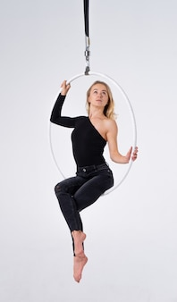 Slim and flexible girl in an aerial hoop isolated on a white background.