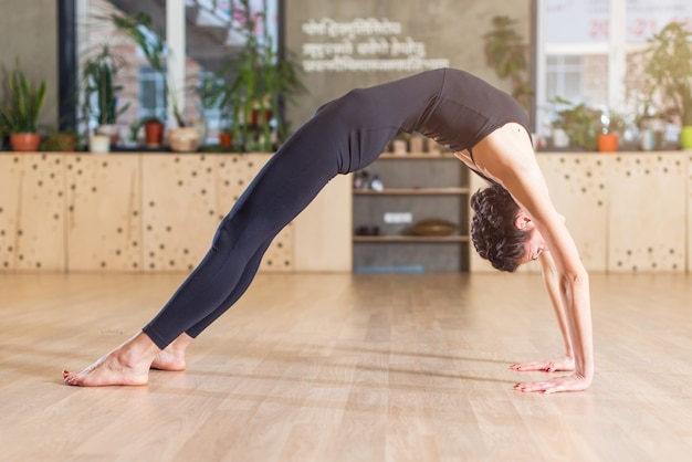 Slim flexible young woman doing yoga exercise standing in bridge position in a gym