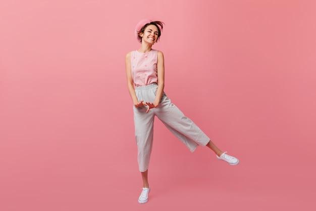 Стройная французская женщина смешно танцует на розовой стене