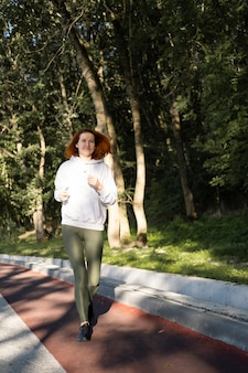 Slim ginger woman in sport clothes running in park on morning healthy fitness lifestyle