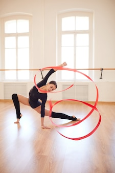Стройная девушка танцует с гимнастической лентой