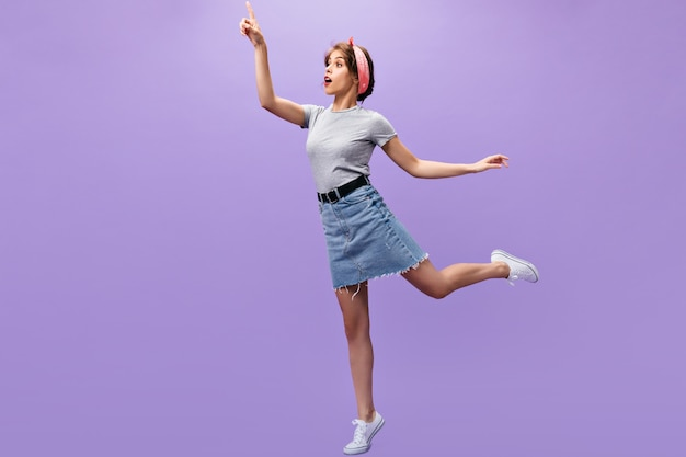 Slim ragazza in abito denim in posa. sfondo viola n. giovane donna sorpresa con bandana rosa in scarpe da ginnastica bianche e camicia alla moda che salta.