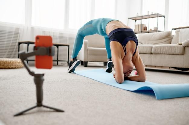 自宅でストレッチ運動をしているスリムな女の子、ラップトップでオンラインフィットトレーニング。スポーツウェア、インターネットスポーツトレーニング、室内インテリアの女性